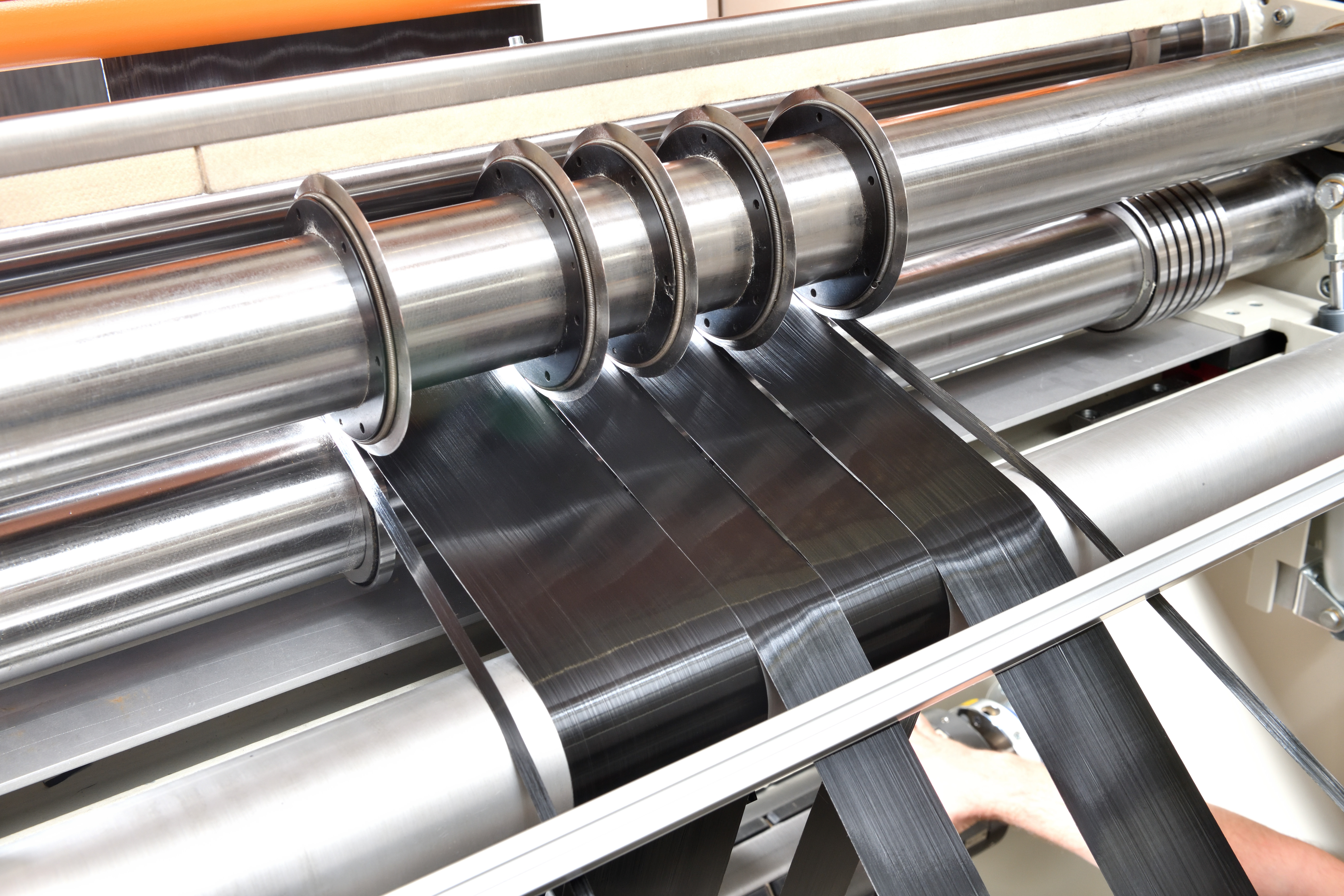 "The picture shows the slitting of carbon fibers by means of the A&M KINZEL Slitting and Rewinding Device ""LS-RR 1000"""